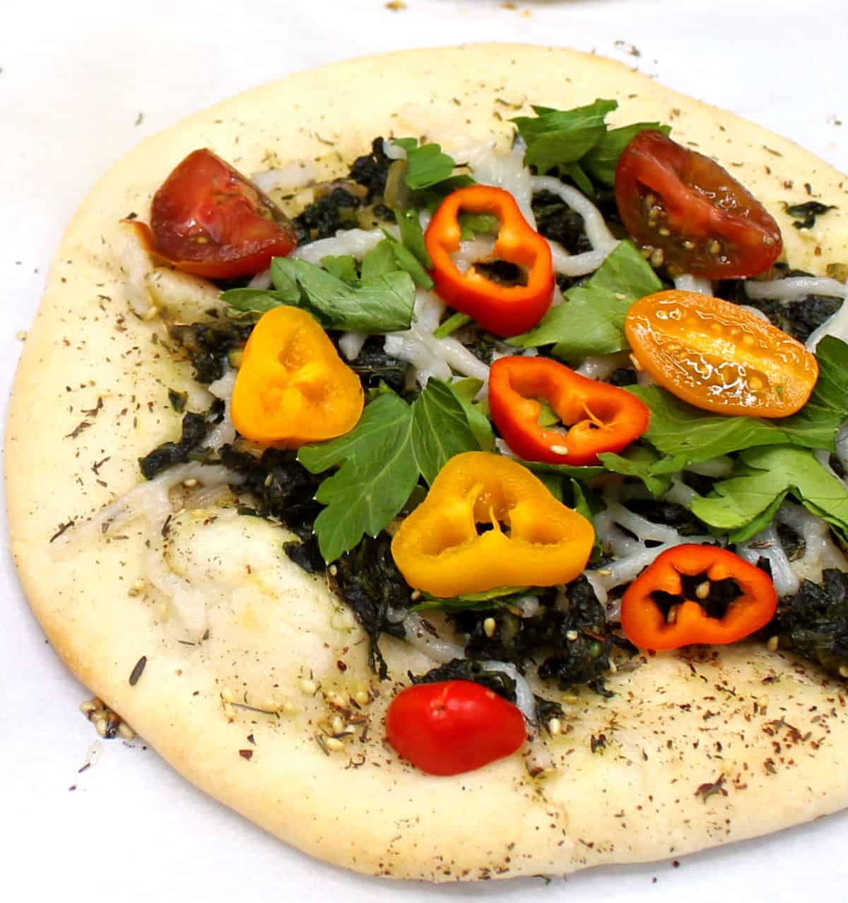 A puffy Lebanese manakish piled with fresh veggies, parsley and a flavorful spinach stuffing ona  white background.