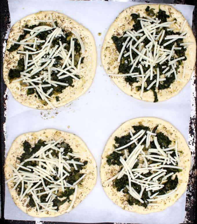 Four manakish flatbreads on a baking sheet with spinach stuffing, za'atar, cheese shreds waiting to be baked