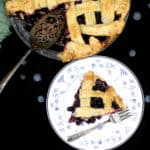 A golden, delicious slice of blueberry pie on a blue and white plate with an intricate design and a fork with the full pie next to it