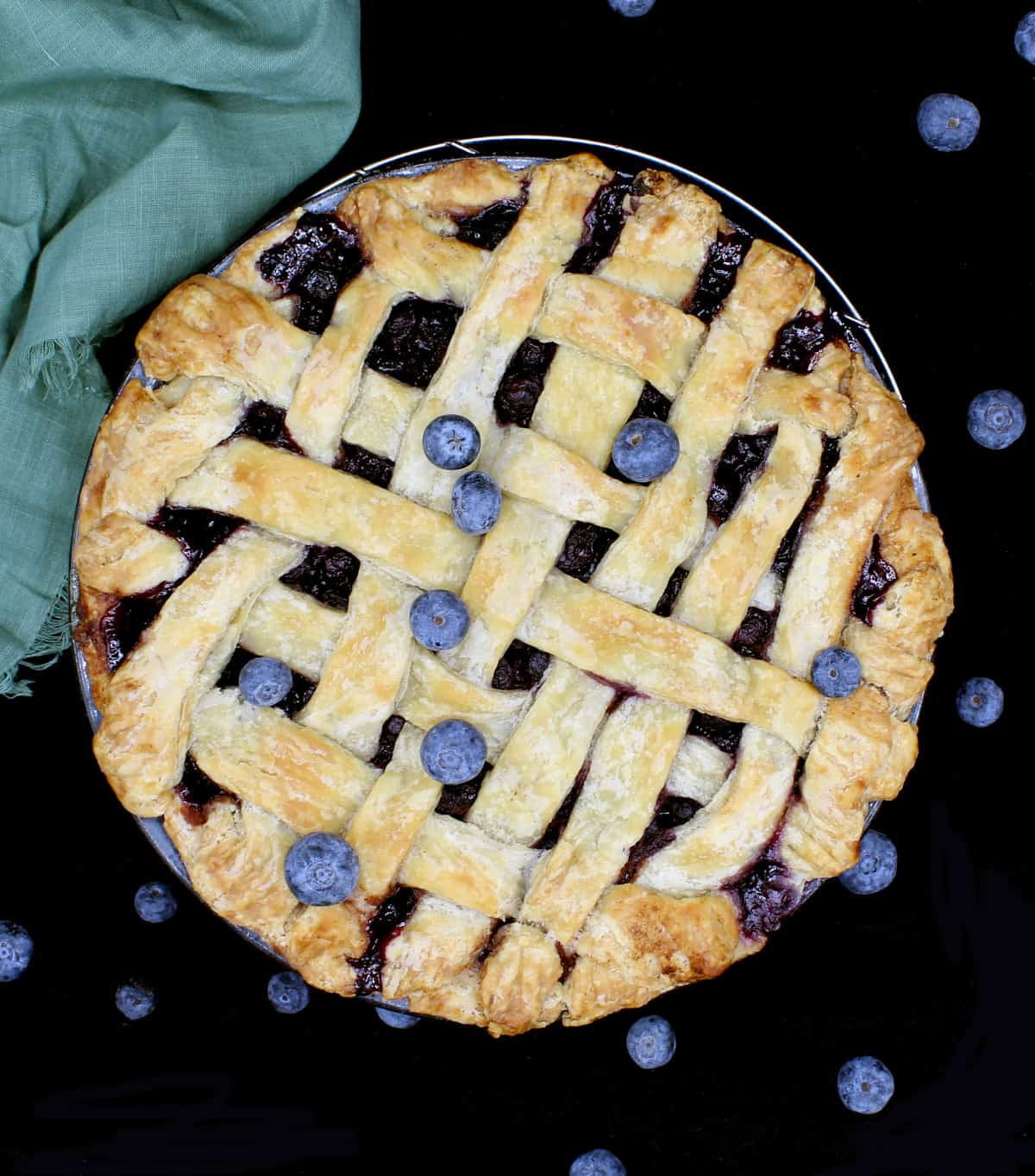 A vegan blueberry pie with a lattice top and filling showing with blueberries scattered around. and a green napkin on a black background.
