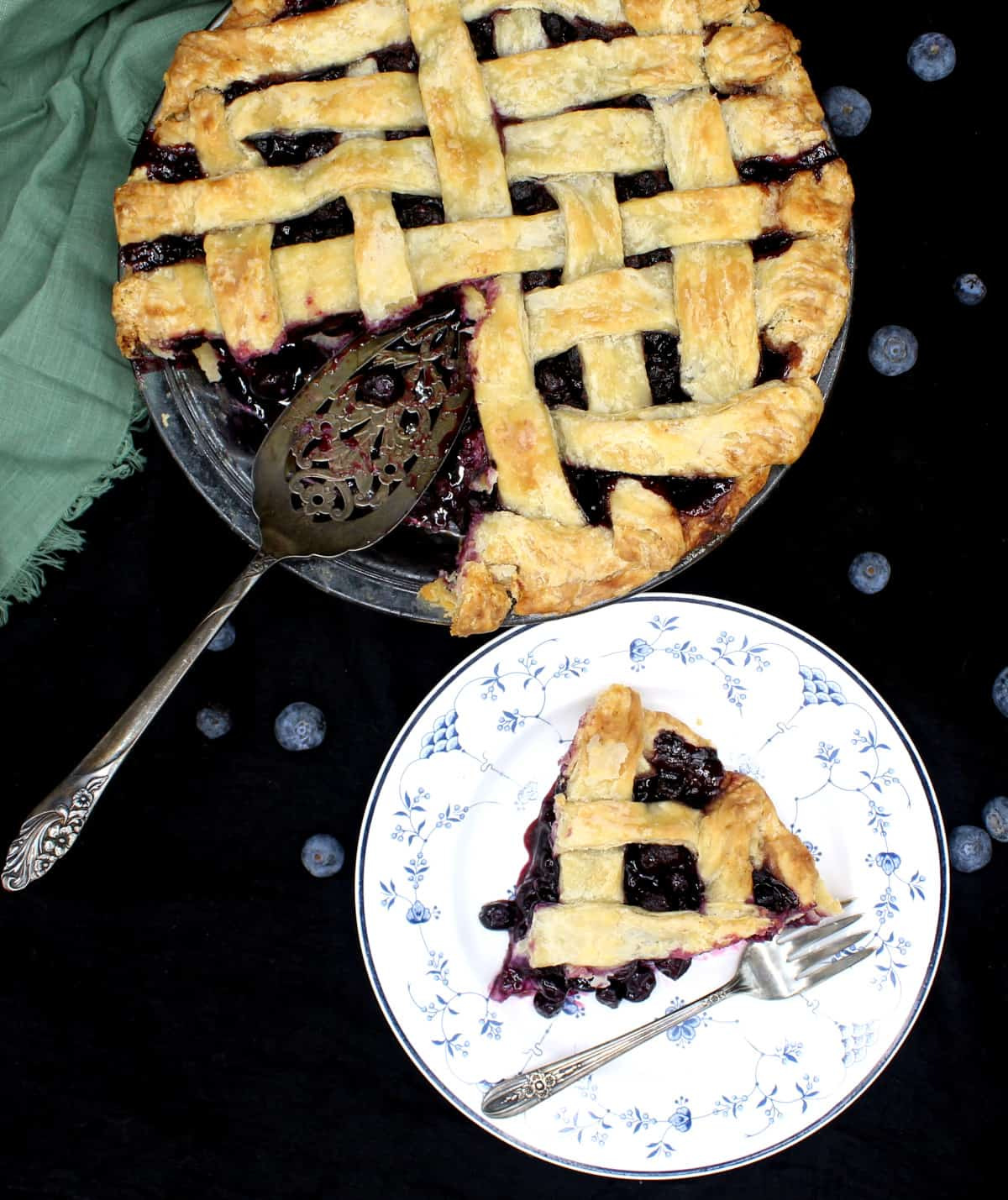 A slice of vegan blueberry pie on a blue and white china plate with a delicate floral pattern and a silver fork with the whole pie next to it and blueberries scattered around.