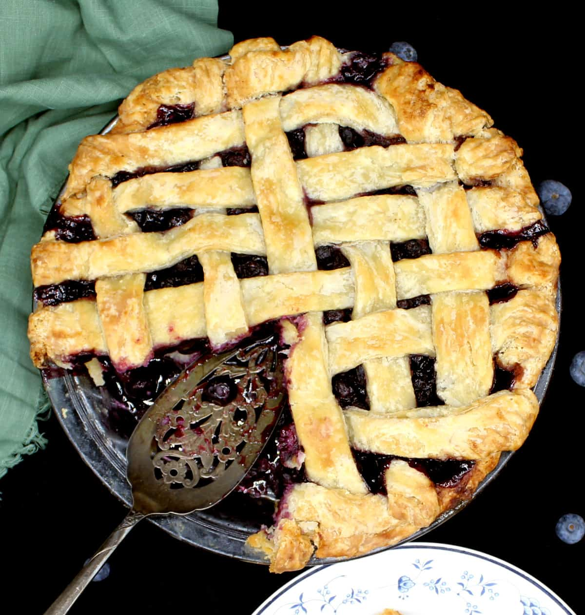 A vegan blueberry pie with a slice cut out and the filling showing with an intricates silver pie server. Blueberries are scattered around and a green napkin lies next to the glass pie plate.