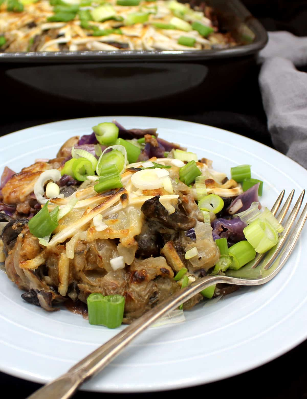 A blue gray dish with a portion of vegan cabbage casserole with meaty vegan beef crumbles, cabbage, potatoes, herbs and vegan mozzarella shreds and scallions scattered on top, with a baking dish and gray napkin in the background.