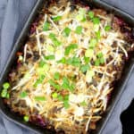 A stoneware gray baking dish with a vegan cabbage casserole with meaty vegan beef crumbles, cabbage, potatoes, herbs and vegan mozzarella shreds and scallions scattered on top, on a gray napkin
