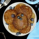 An overhead shot of a plate filled with vegan glutenfree coconut flour pancakes with blueberries and next to it are a bowl of blueberries, a blue napkin, a kinfe and fork.