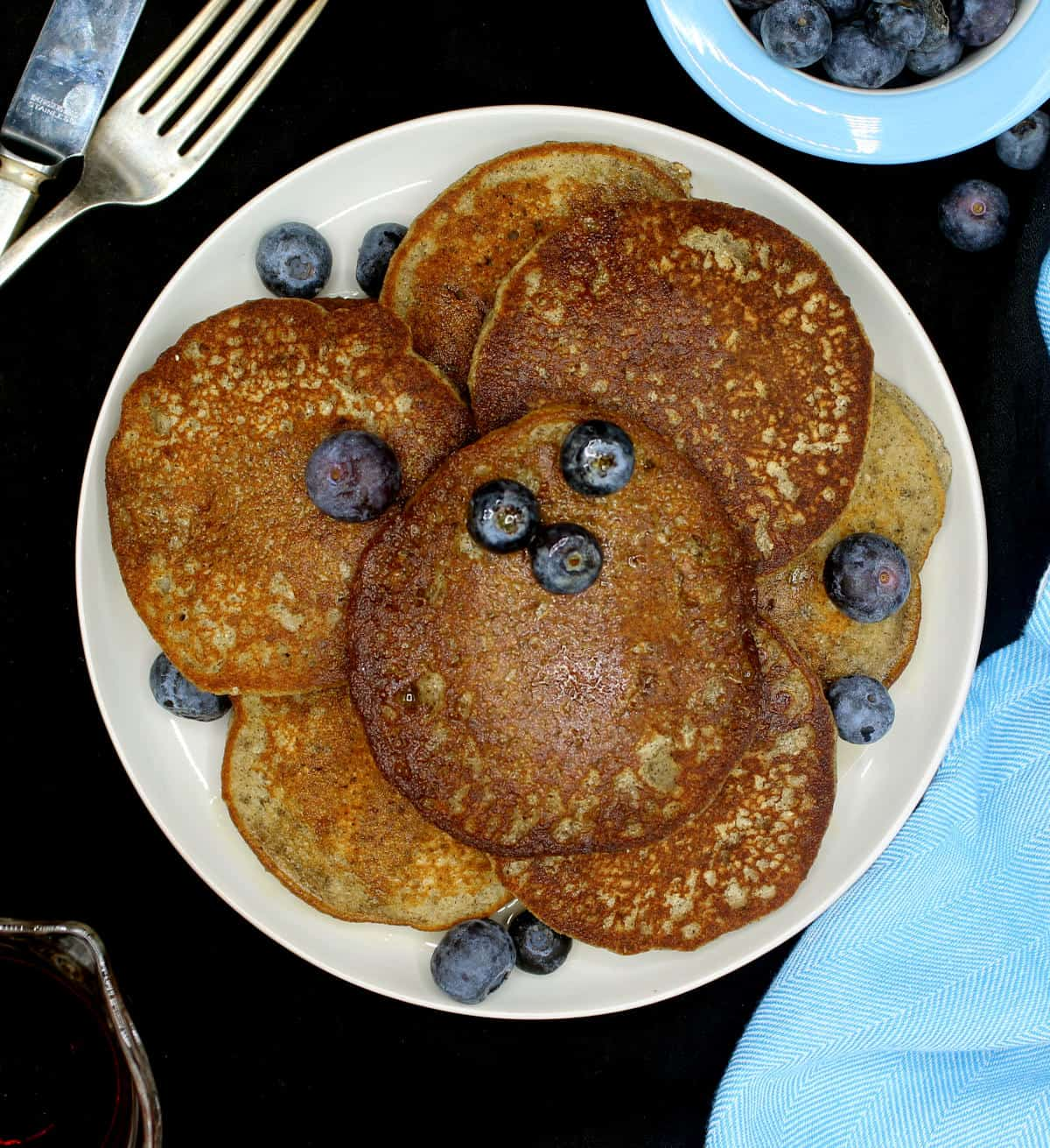 An overhead shot of gf vegan coconut flour pancakes on a plate with blueberries, knife and fork, maple syrup and blue napkin.