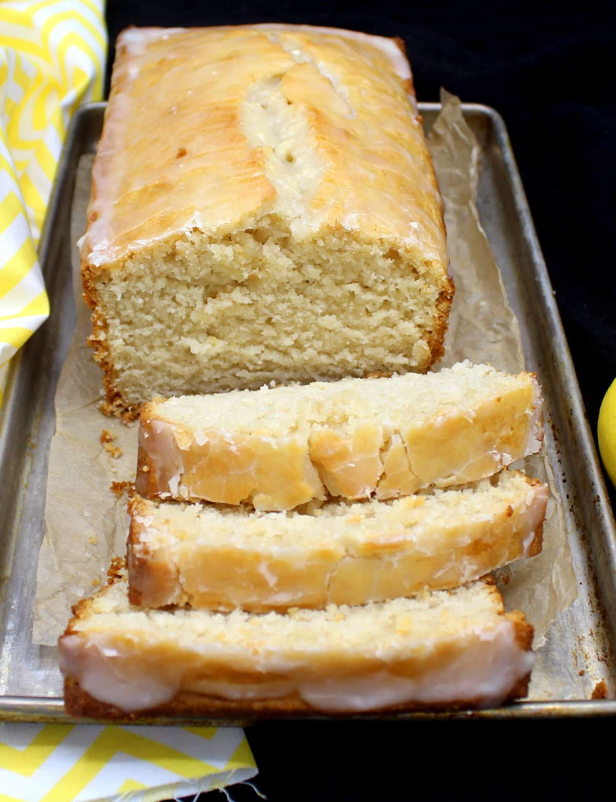 A loaf of buttery vegan lemon pound cake on a metal baking tray with slices cut in front of it and showing the dense, soft crumb. Next to it are lemons and a yellow and white napkin.