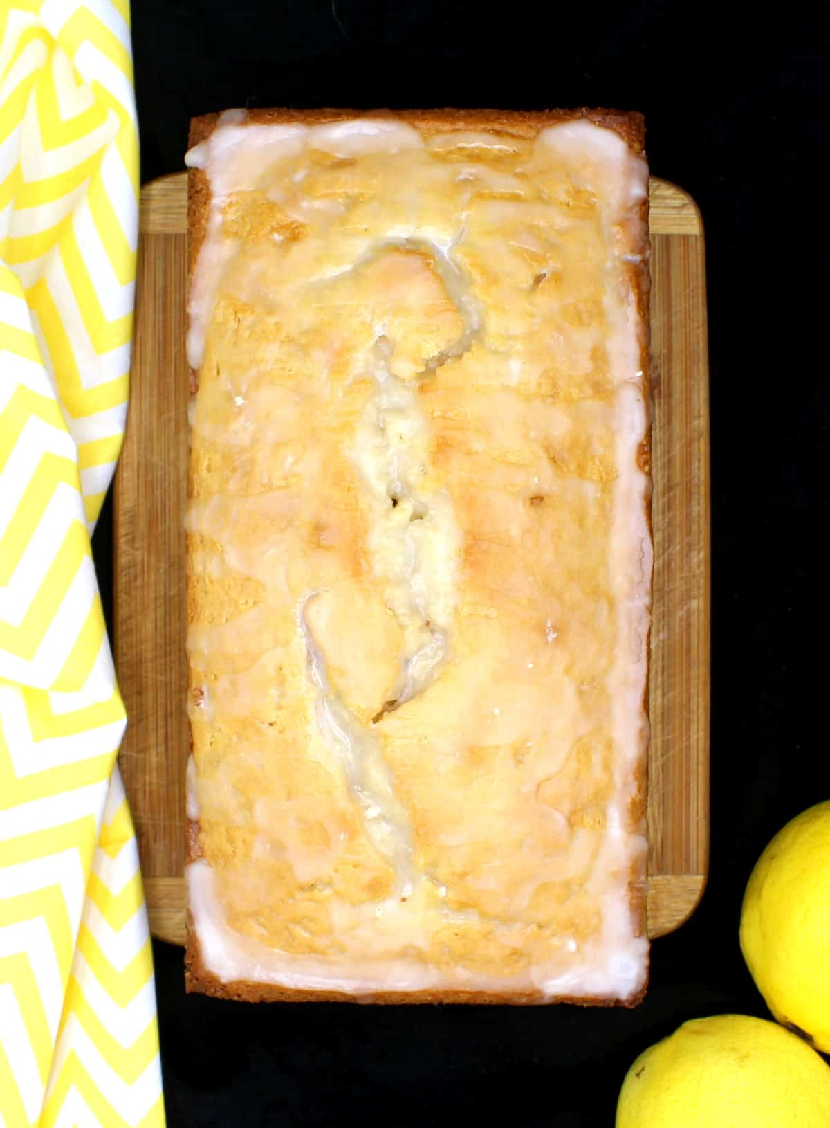 A whole loaf of buttery vegan lemon pound cake on a metal baking tray. Next to it are lemons and a yellow and white napkin.