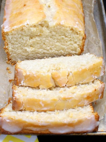 A loaf of vegan lemon pound cake with three slices cut and showing the dense, soft crumb on a metal pan with lemons and a yellow and white napkin