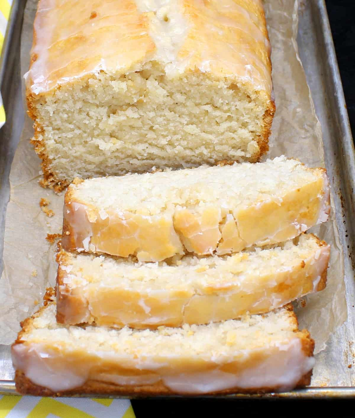 A loaf of buttery vegan lemon pound cake on a metal baking tray with slices cut in front of it and showing the dense, soft crumb.