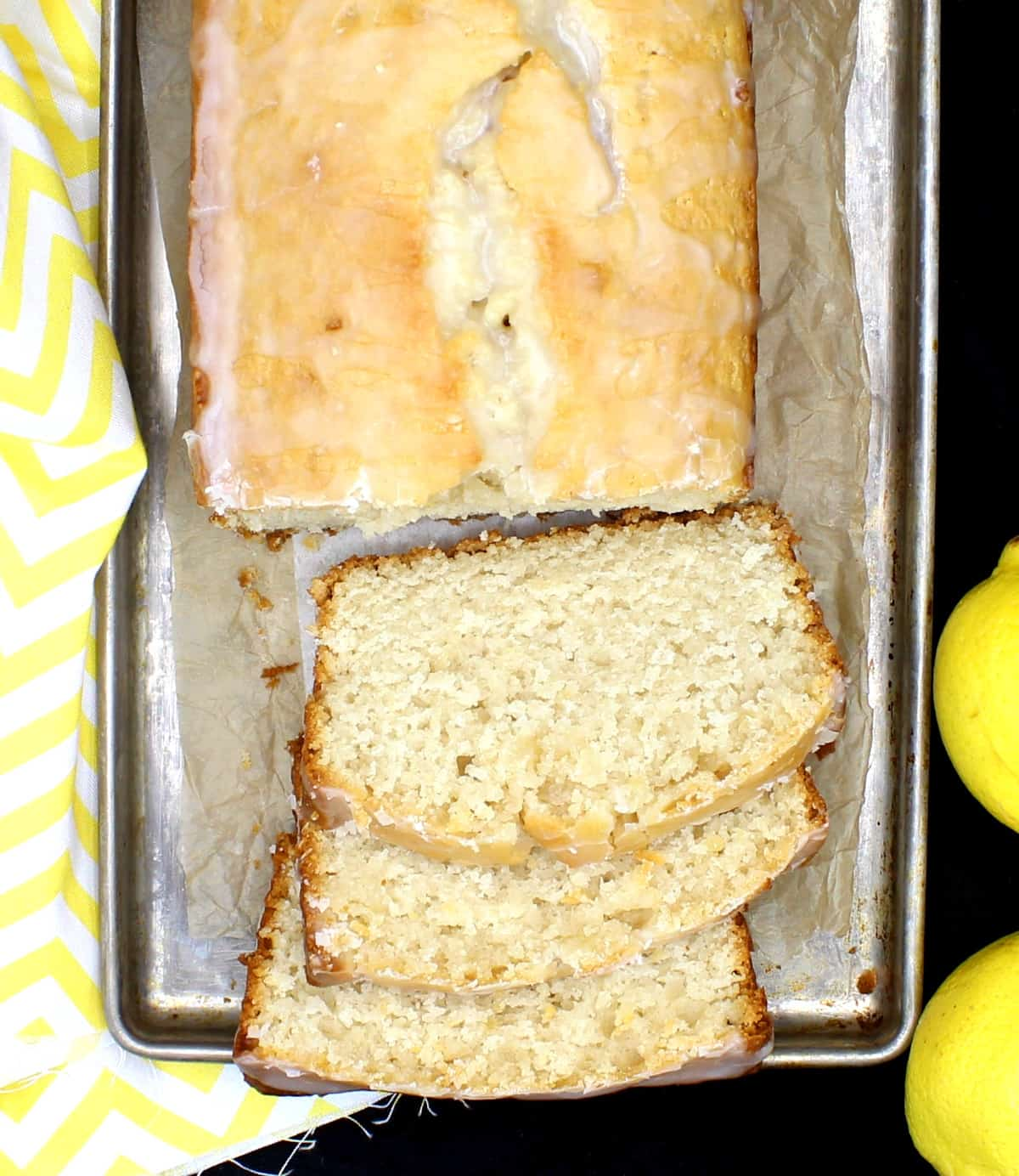 Um pedaço de bolo de limão vegano amanteigado em uma assadeira de metal com fatias cortadas na frente e mostrando o miolo denso e macio.  Ao lado estão limões e um guardanapo amarelo e branco.