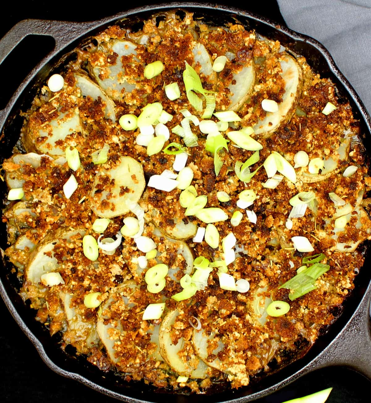 Vegan spinach potato casserole in a cast iron skillet topped with breadcrumbs and scattered with scallions on a black background.