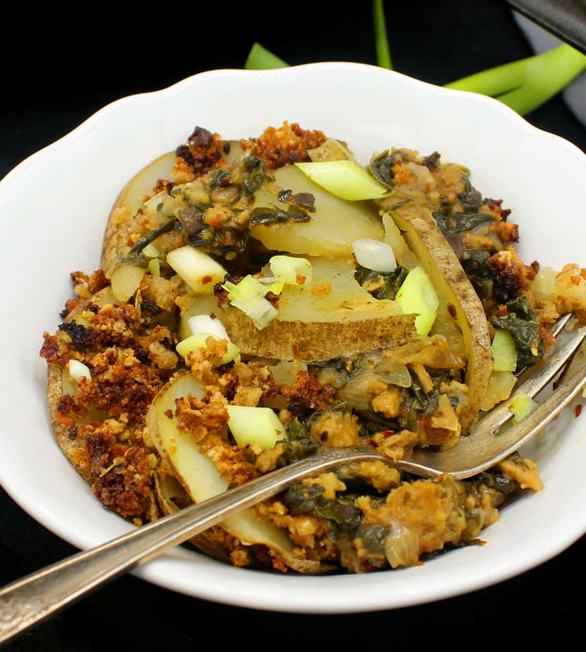 A white ceramic bowl with a serving of vegan spinach potato casserole with sausage and a fork. Scallions are scattered on top and on the side.