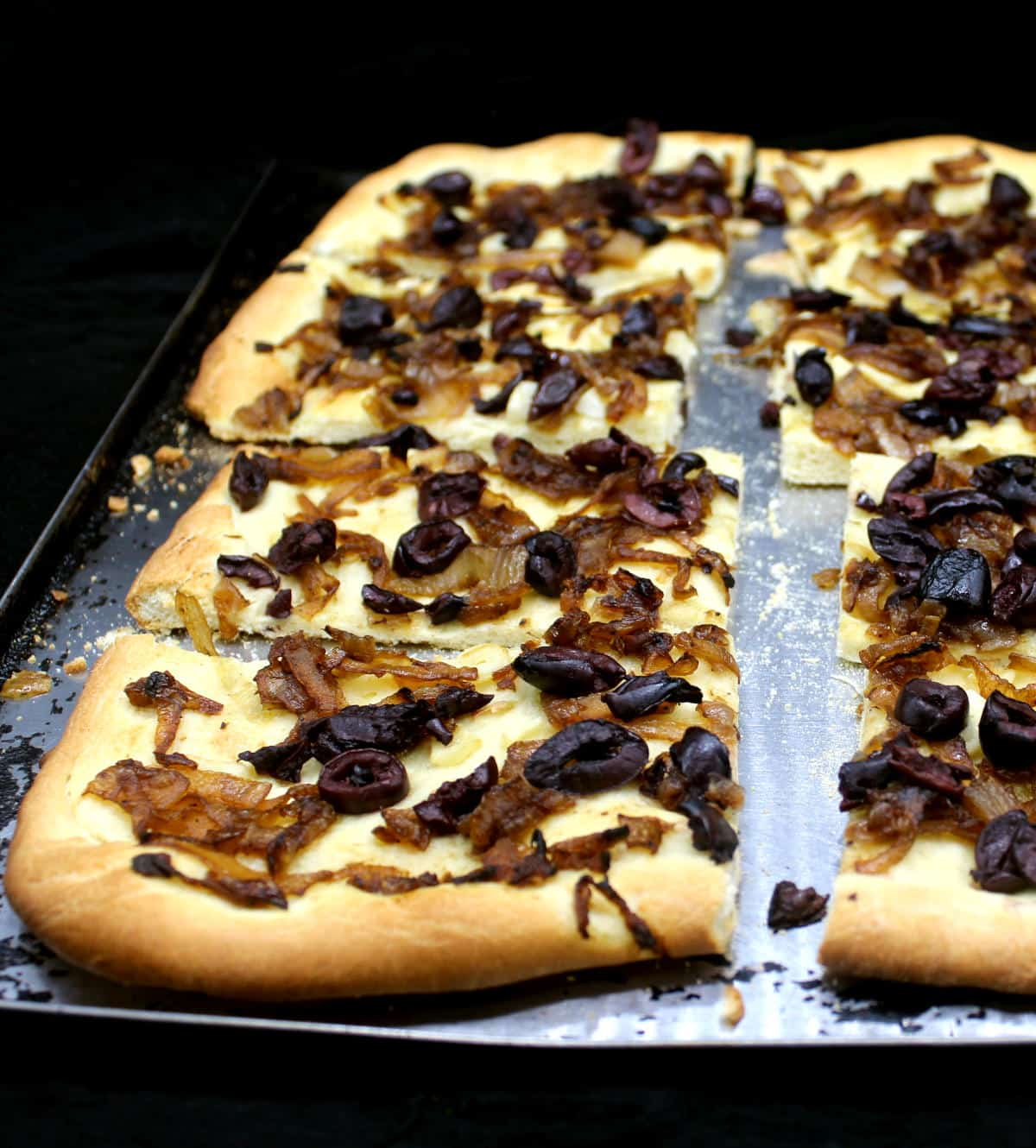 Closeup of slices of caramelized onion tart with olives on a baking sheet.