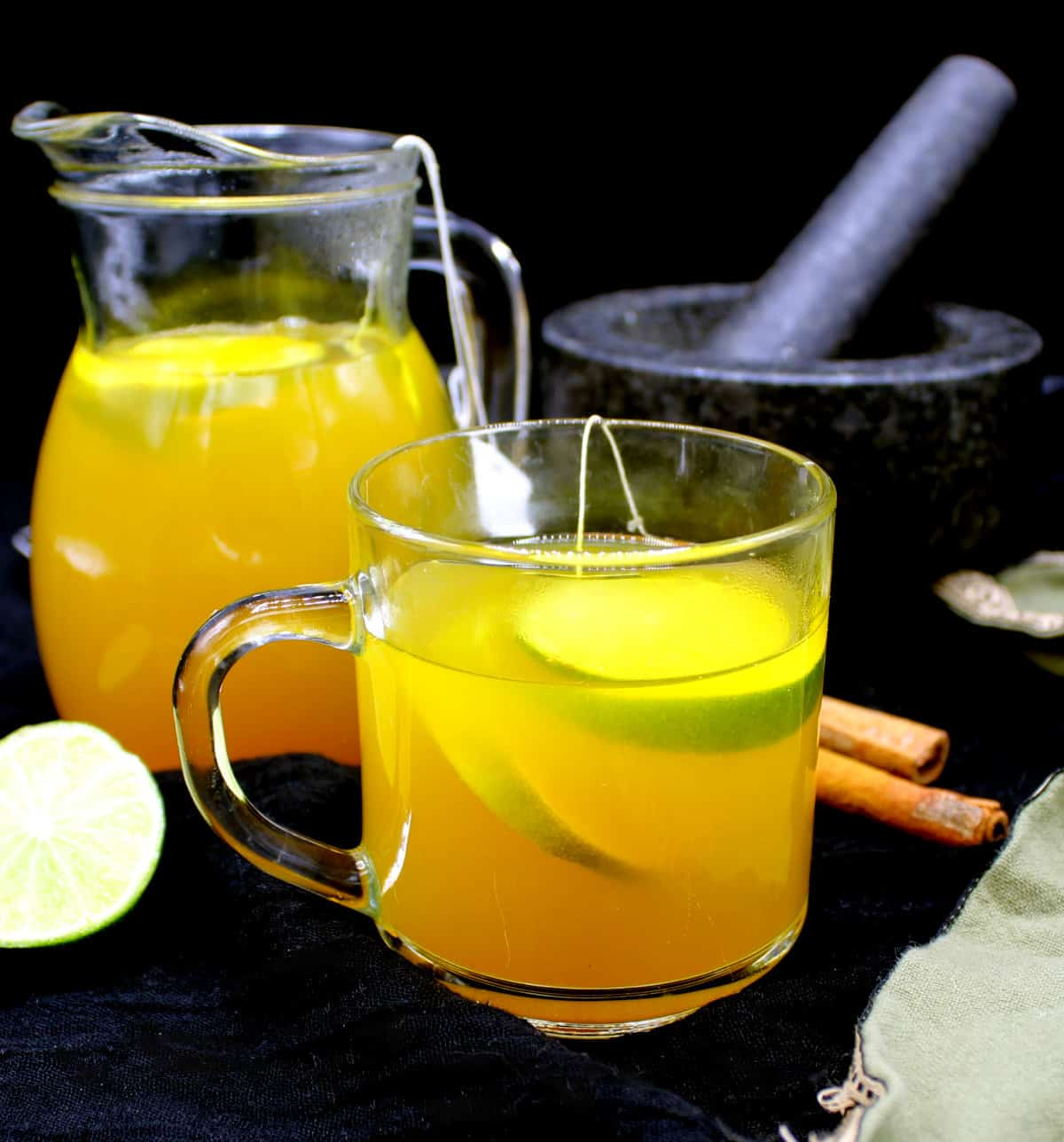 Ginger turmeric tea in a cup and a pitcher with ginger, cardamom, cinnamon, lemons and black pepper.