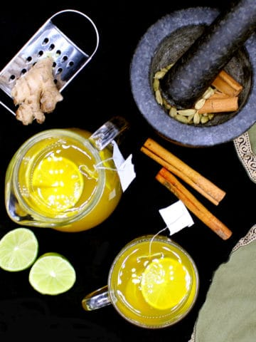 Turmeric Ginger Tea with ingredients used for making it including spices in a mortar and pestle and limes