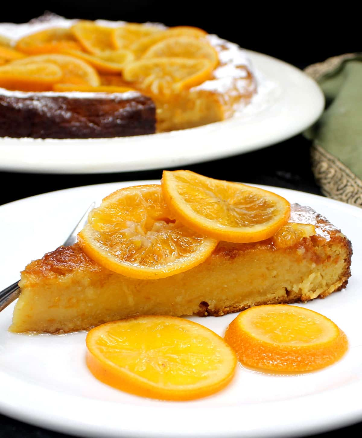 A close up of a slice of vegan clementine cake with candied clementine slices on a white plate with the full cake behind.