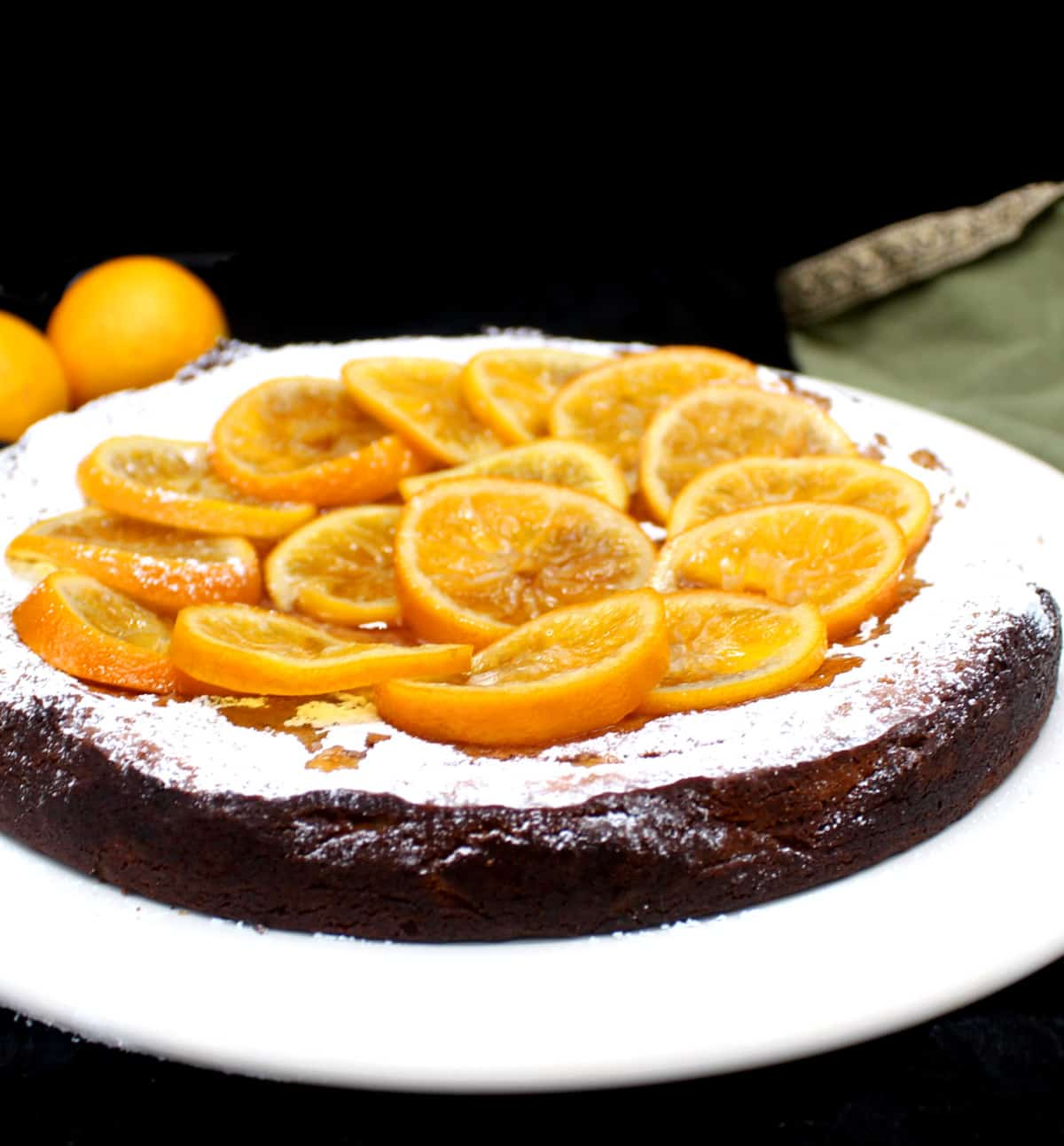Front shot of whole vegan clementine cake on a white plate topped with candied clementines.