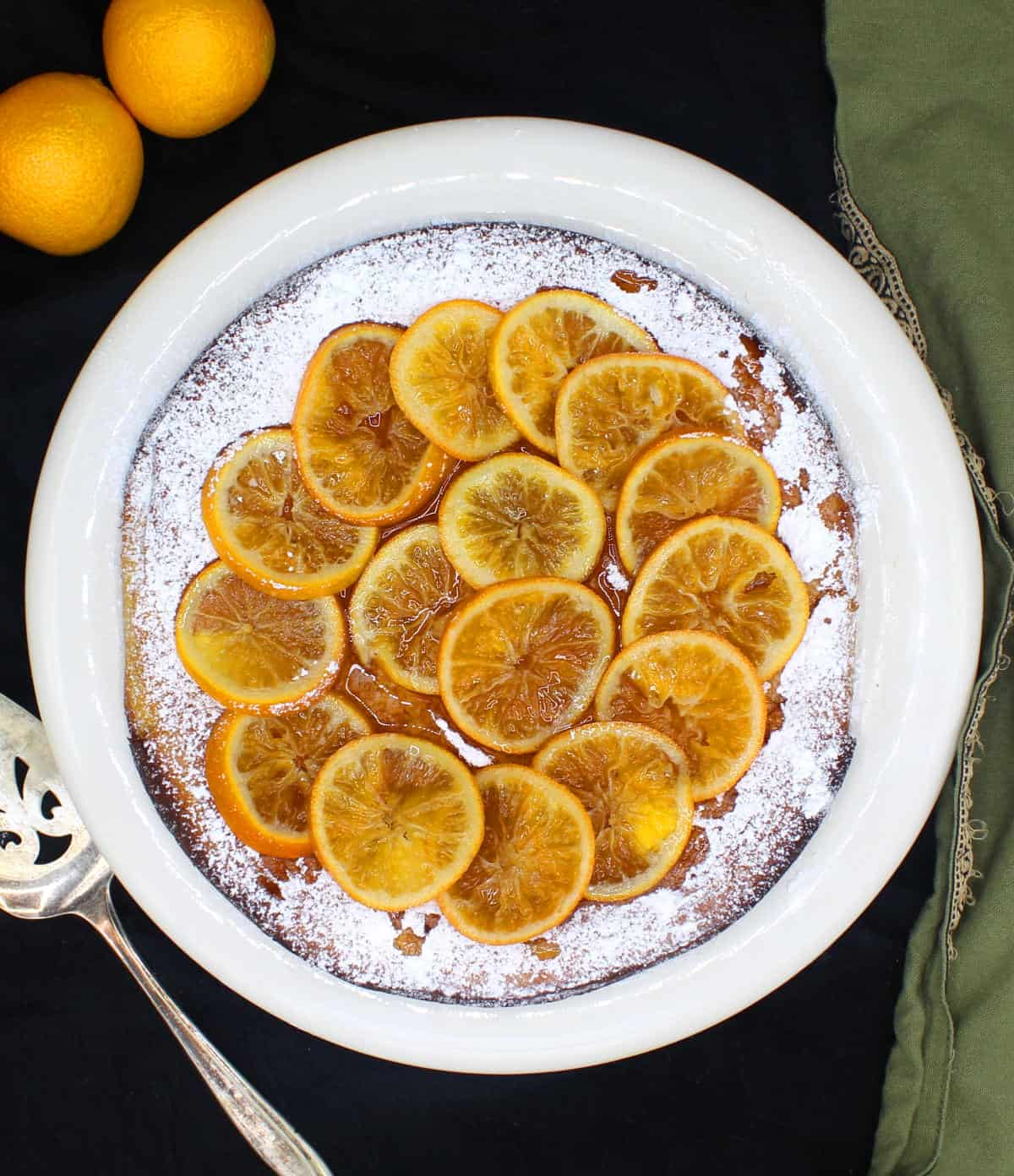 Overheat shot of a pretty glutenfree clementine cake on a white plate with mandarins next to it and a cake server.