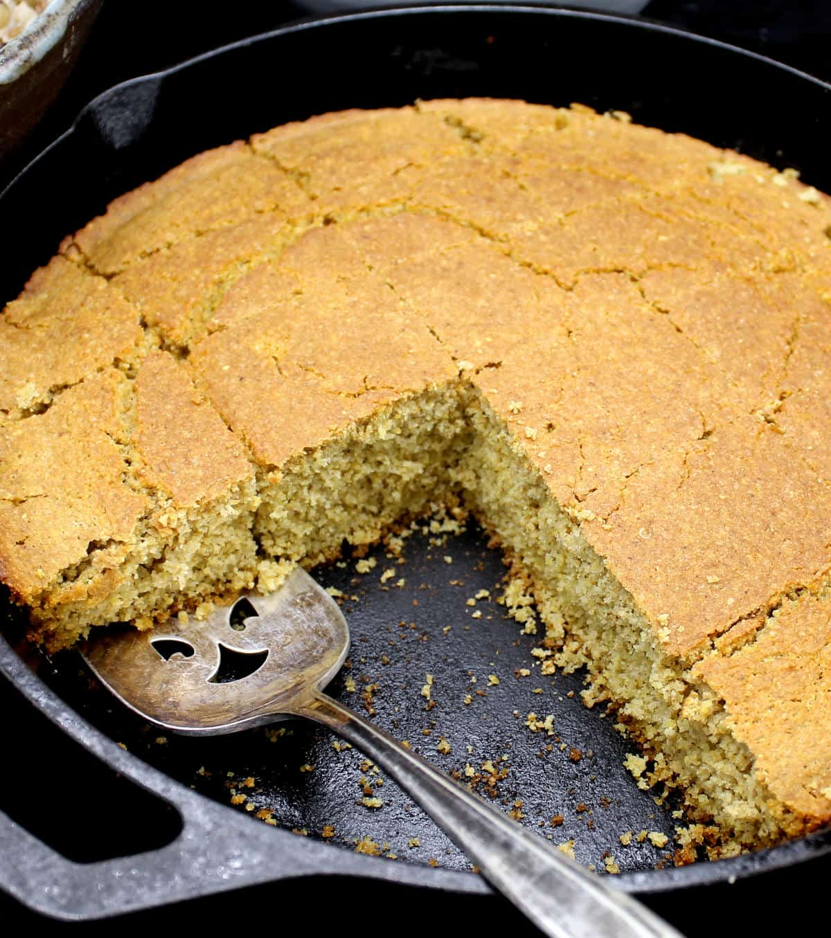Cross section of vegan cornbread in a cast iron skillet.