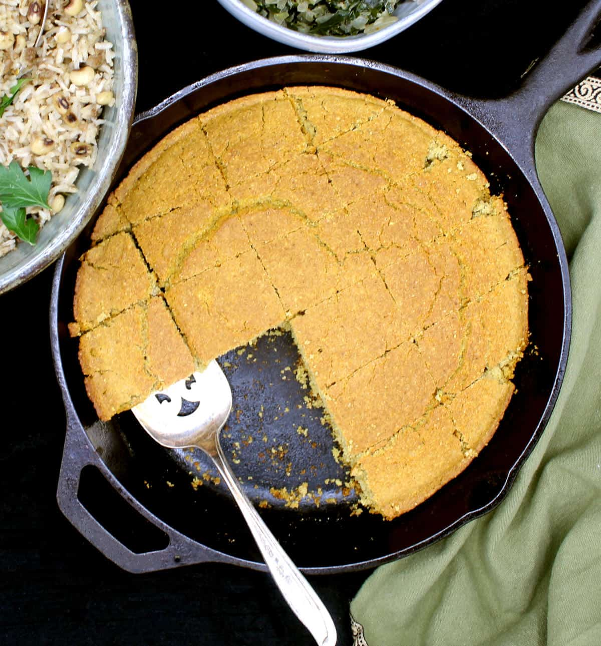 Vegan cornbread made southern style in a cast iron skillet and served with collard greens and Hoppin' John.