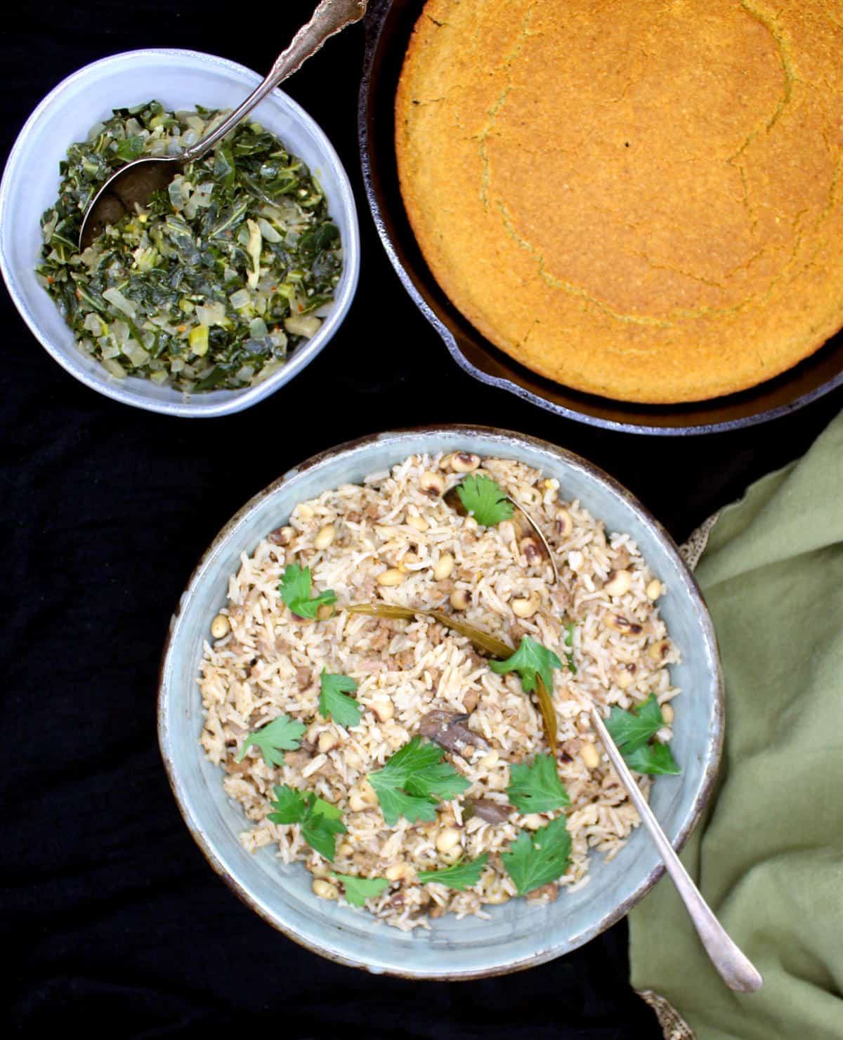 Vegan corn bread in a cast iron skillet, with collard greens and hoppin' John in bowls.