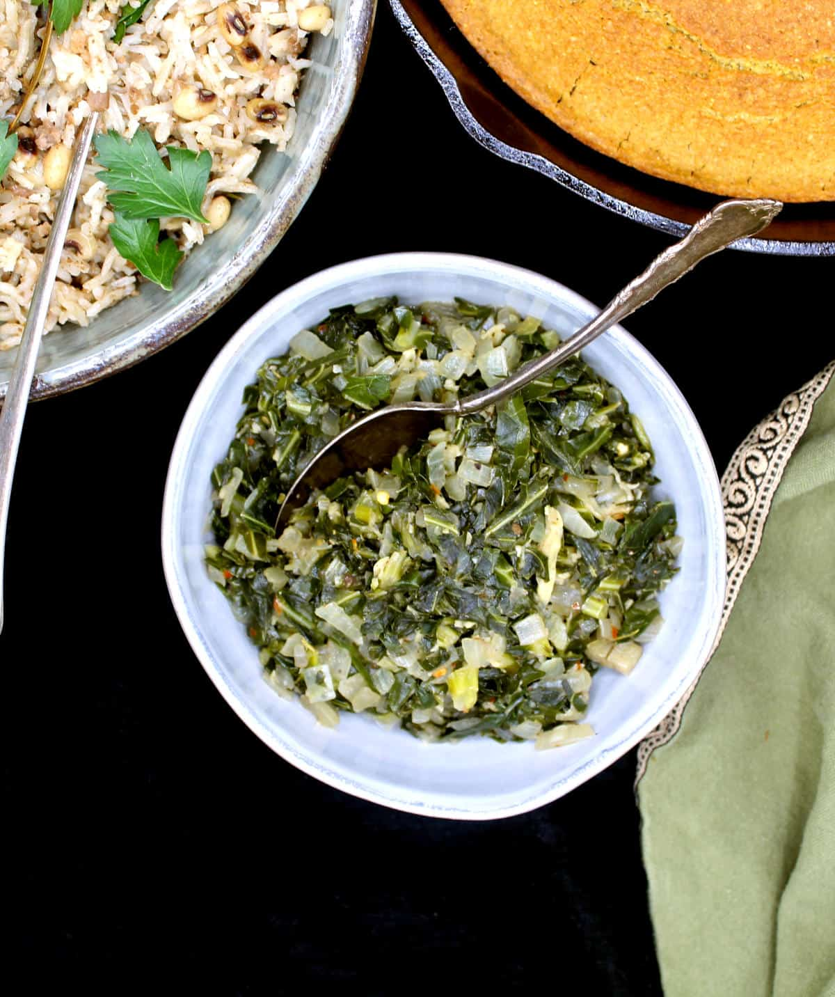 Braised southern style collard greens in a ceramic gray bowl with a silver spoon, vegan cornbread and vegan Hoppin' John.