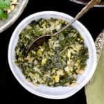 A closeup of braised southern style collard greens in a ceramic gray bowl with a silver spoon.