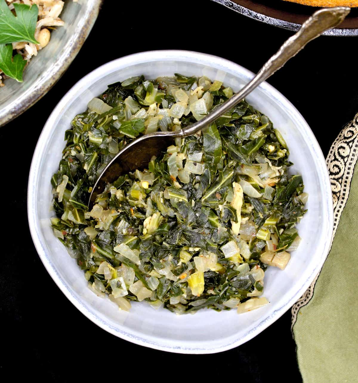 Collard greens cooked southern style with onions, garlic, allspice and rosemary, served in a gray ceramic bowl with a spoon and a green napkin next to it.