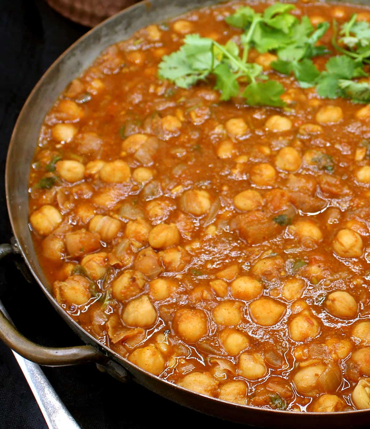 Partial closeup of Indian chana masala in a copper pot with cilantro garnish.