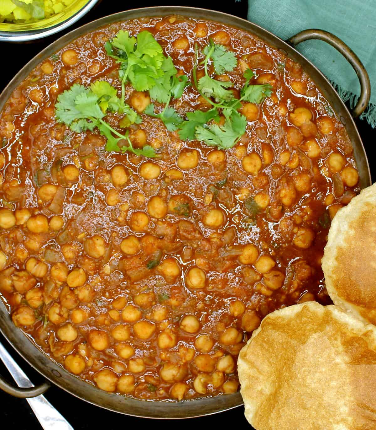 Closeup of chana masala in a copper pan garnished with cilantro and with pooris, an Indian fried bread and potato curry.