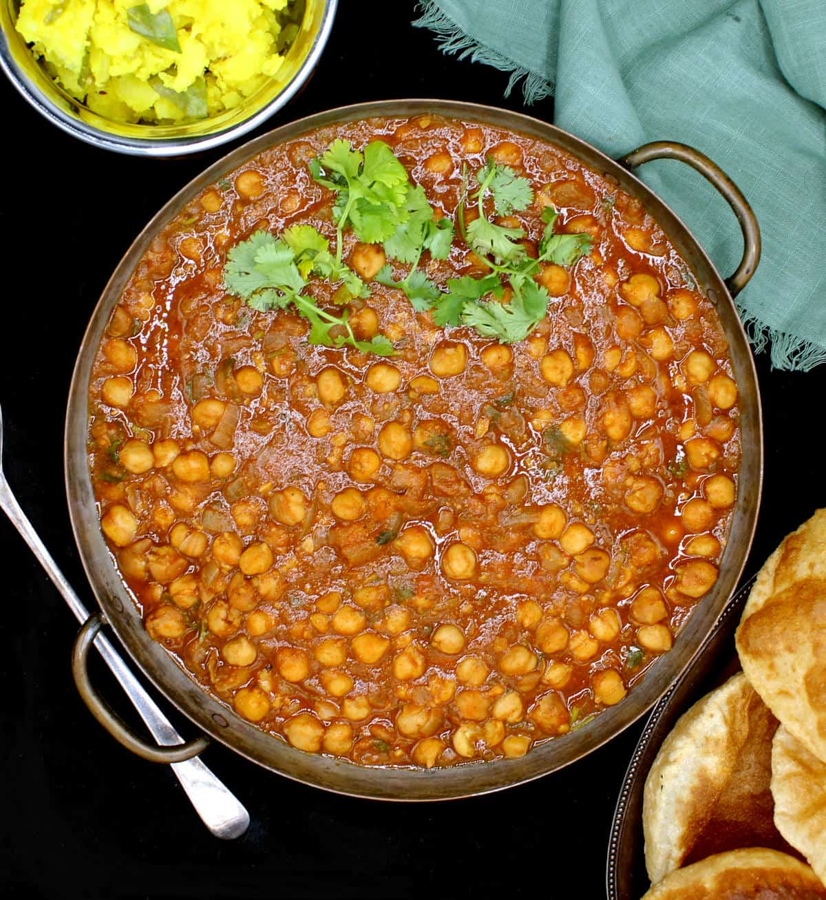 Overhead shot of chana masala in copper pan with serving spoon, potato curry and pooris.