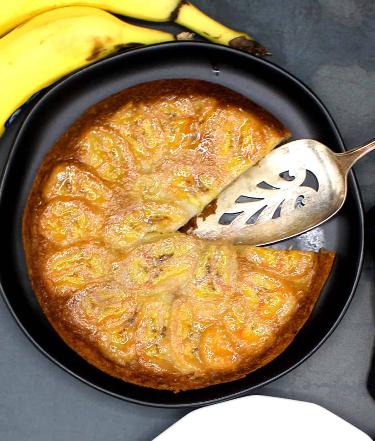 A rich, golden banana upside down cake with a single slice removed, a silver serving spoon and bananas on gray background.