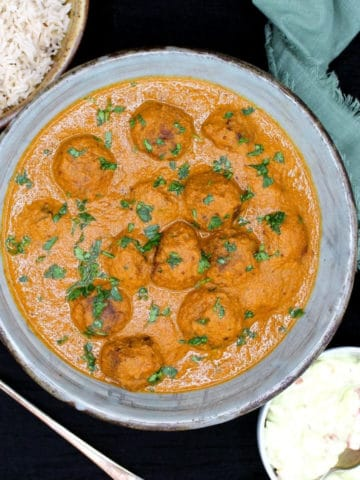Vegan meatball curry with south Indian coconut sauce in a bowl with rice and raita