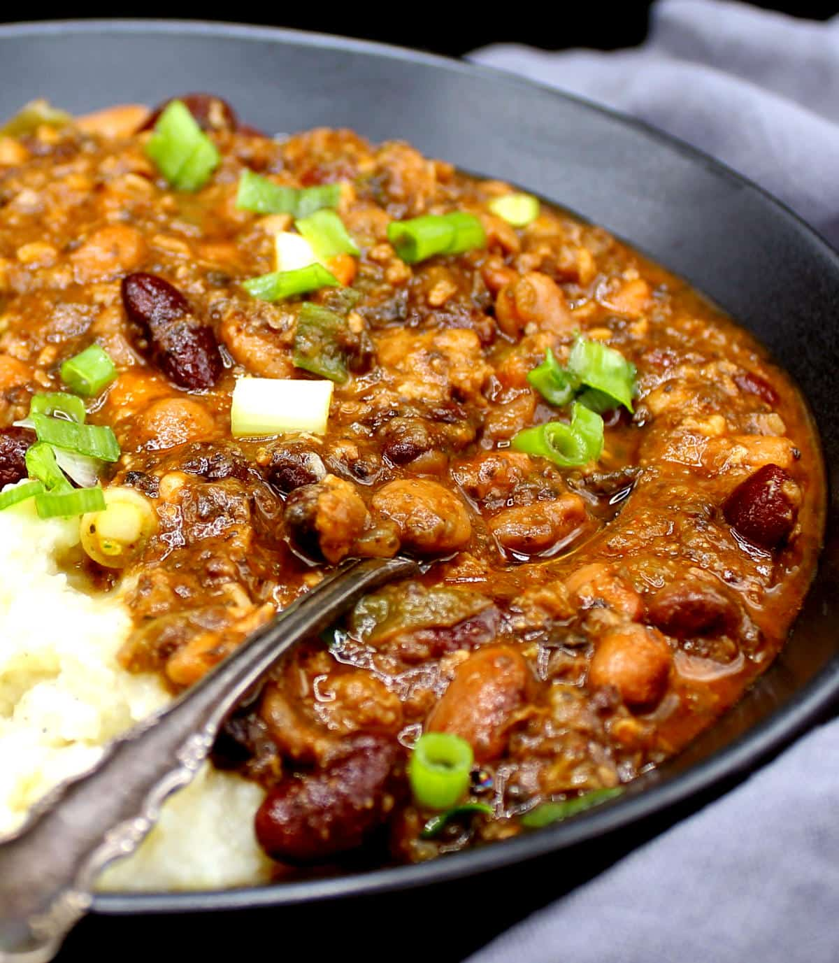 Vegan chili in a black bowl with a spoon and mashed potatoes and spring onions.