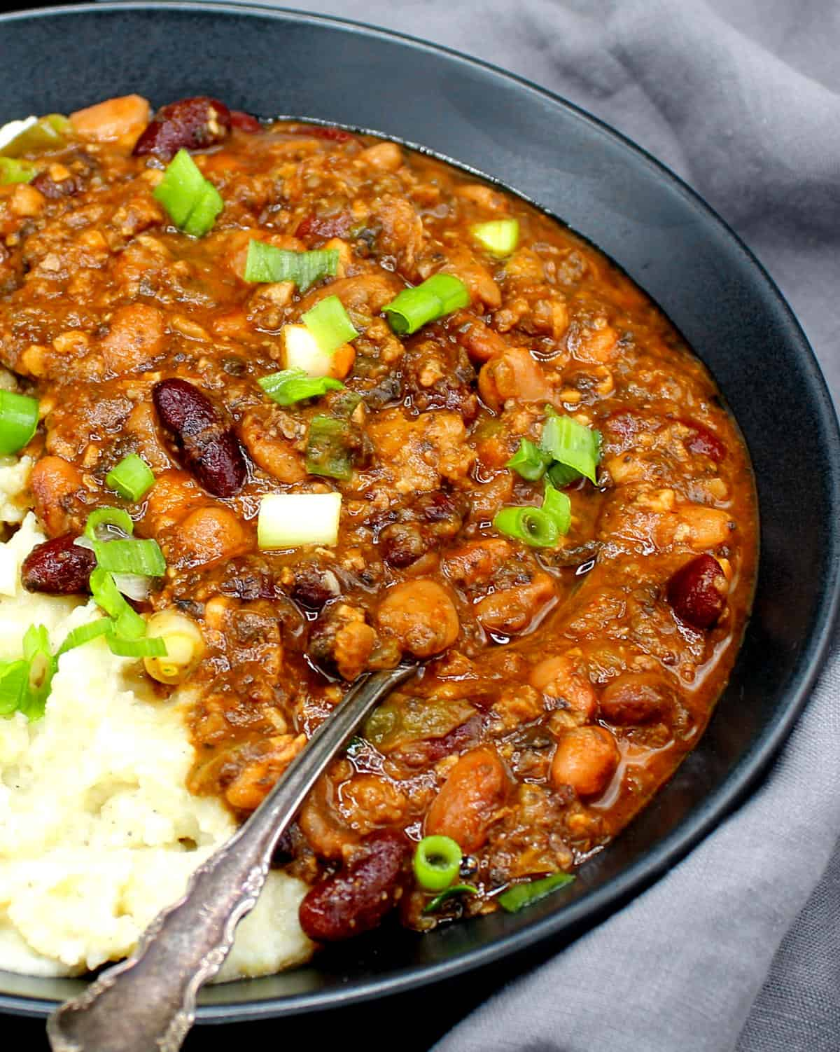 Vegan chili in a black bowl with creamy vegan mashed potatoes and scallions.