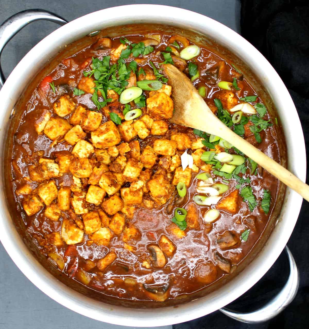 A vegan etouffee with Cajun-seasoned tofu, scallions, parsley and vegies in a steel pot with a wooden spoon.
