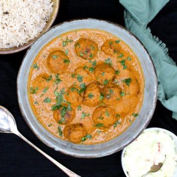 Overhead shot of vegan meatball curry with cumin rice and onion tomato raita and a green napkin
