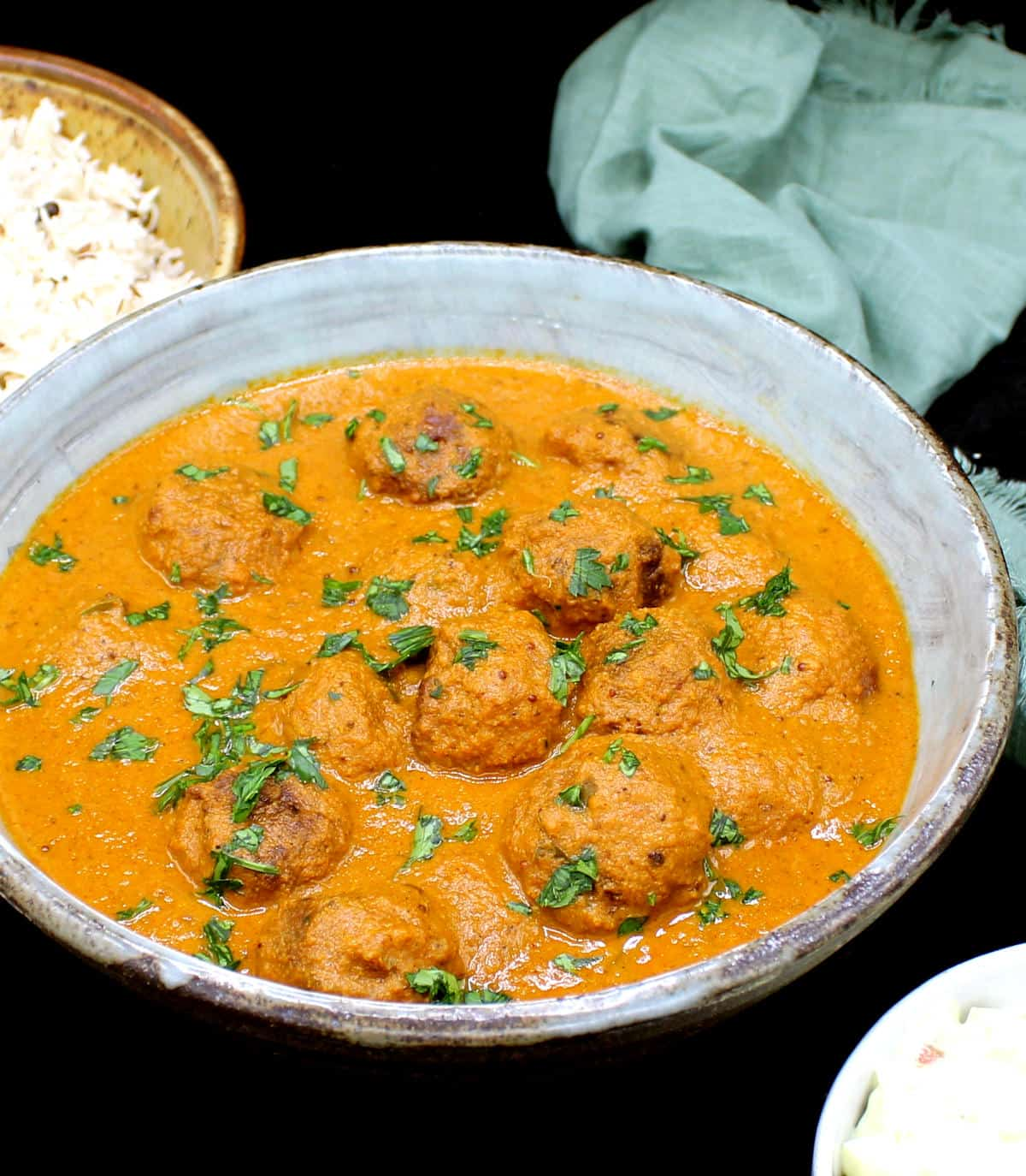 Front shot of Indian meatball curry with rice and raita in bowls.