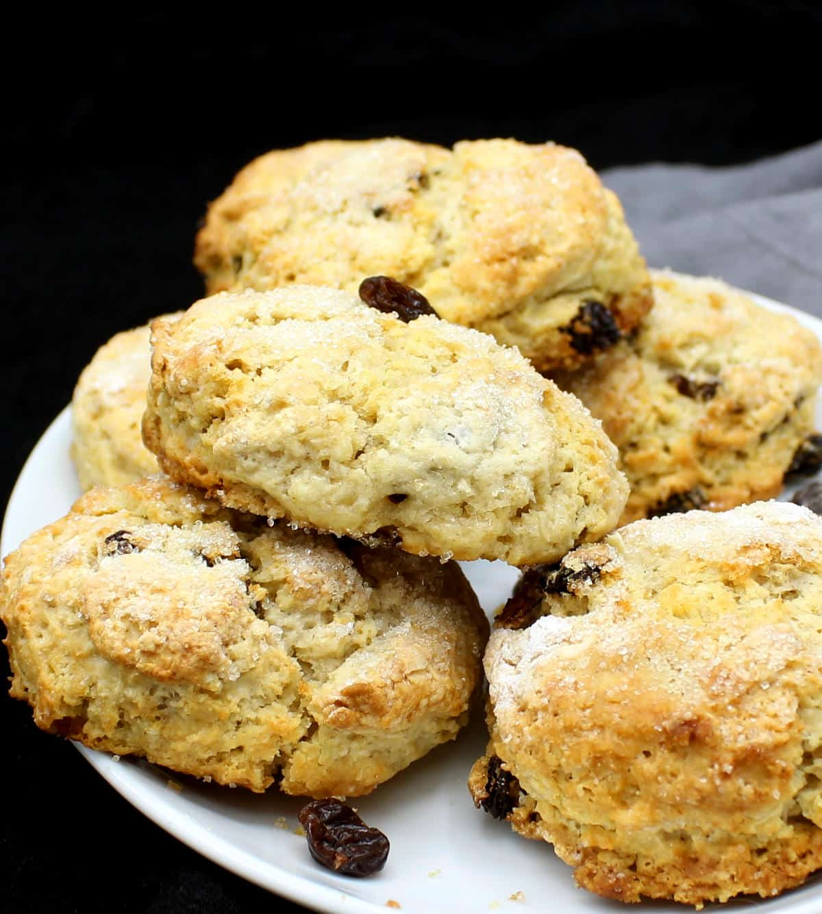 A stack of the best, fluffy, flaky and delicious golden vegan scones in a white plate.