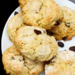 A stack of fluffy vegan currant scones in a white plate with black currants or raisins