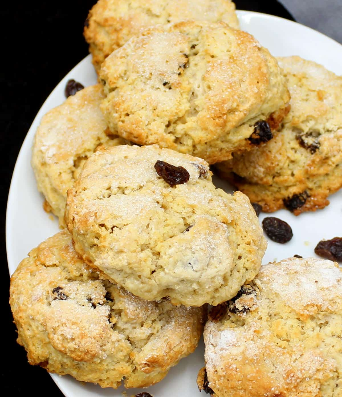 Golden, flaky vegan scones stacked on a white plate with currants.