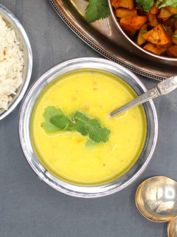 Moong dal in copper and steel serving bowl with aloo sabzi and rice