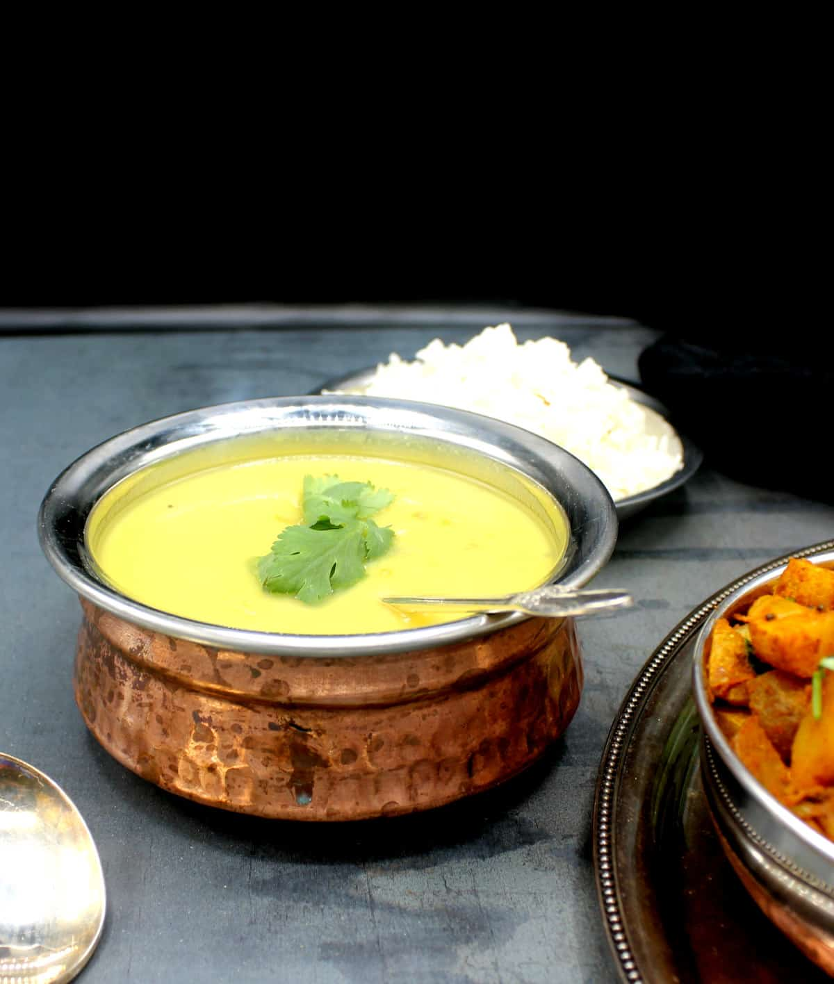 Creamy moong dal in a copper and steel serving bowl with a silver spoon and rice and Bombay potato sabzi on the side.