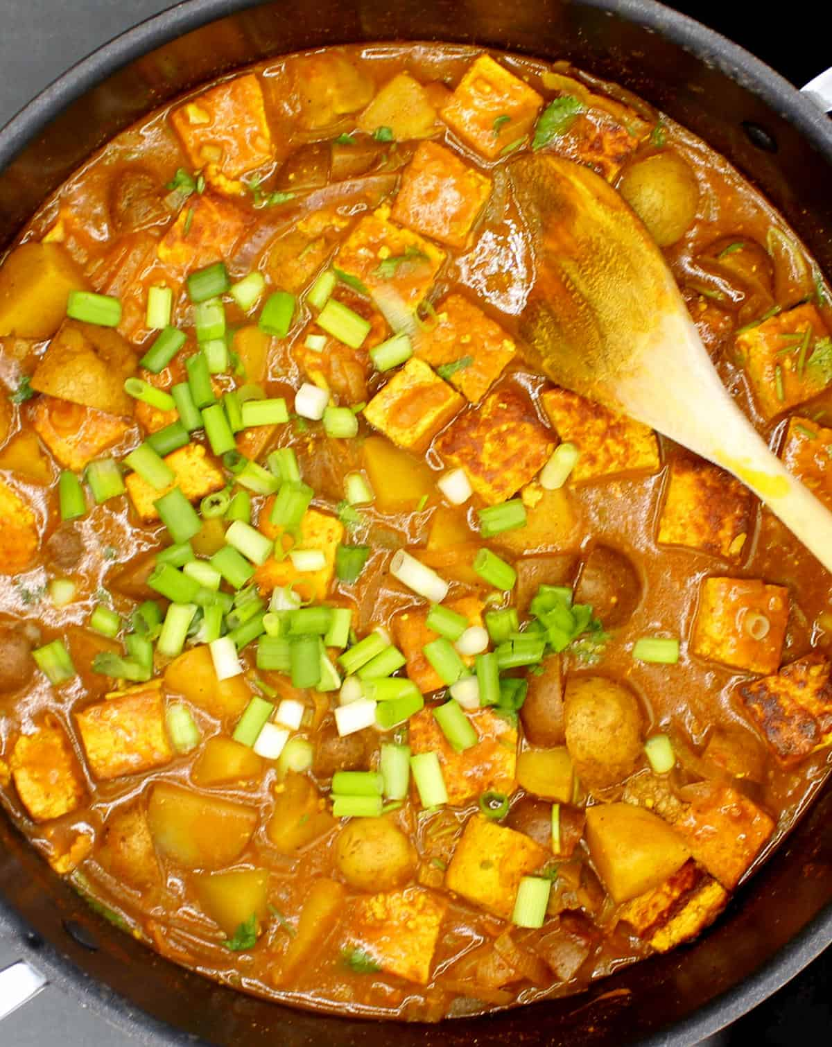 Jamaican Curry with tofu and potatoes in a black saucepan with a wooden ladle and scallions.