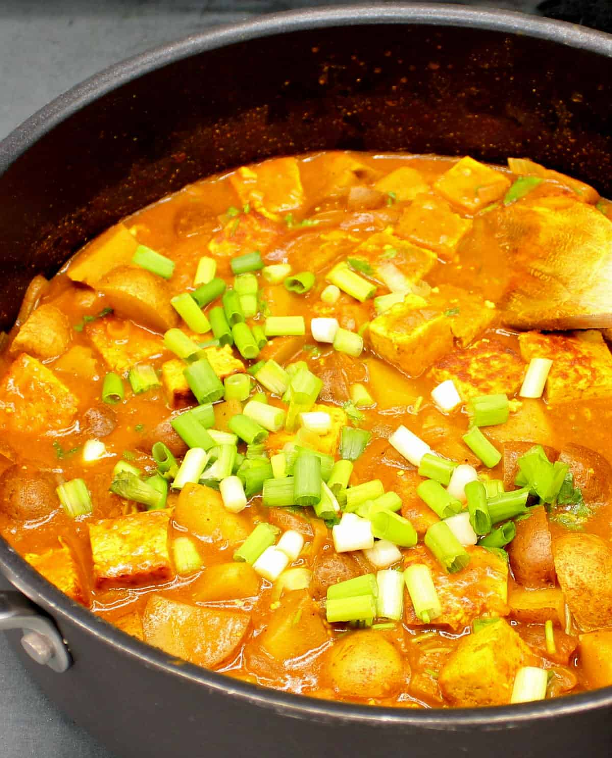 Vegan Jamaican Curry with pan fried tofu and potatoes and scallions in a skillet.