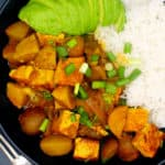 Vegan Jamaican Curry with potatoes, tofu served with rice and avocado