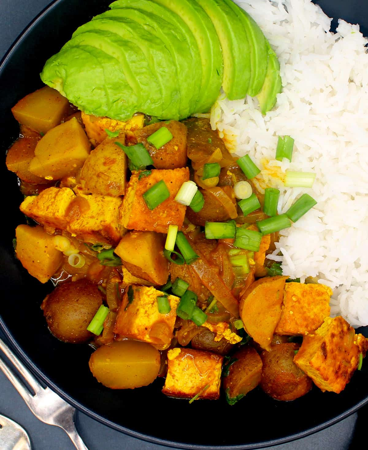 Closeup of Vegan Jamaican Curry with tofu and potatoes in a black bowl with scallions, avocado slices and white rice and two forks.