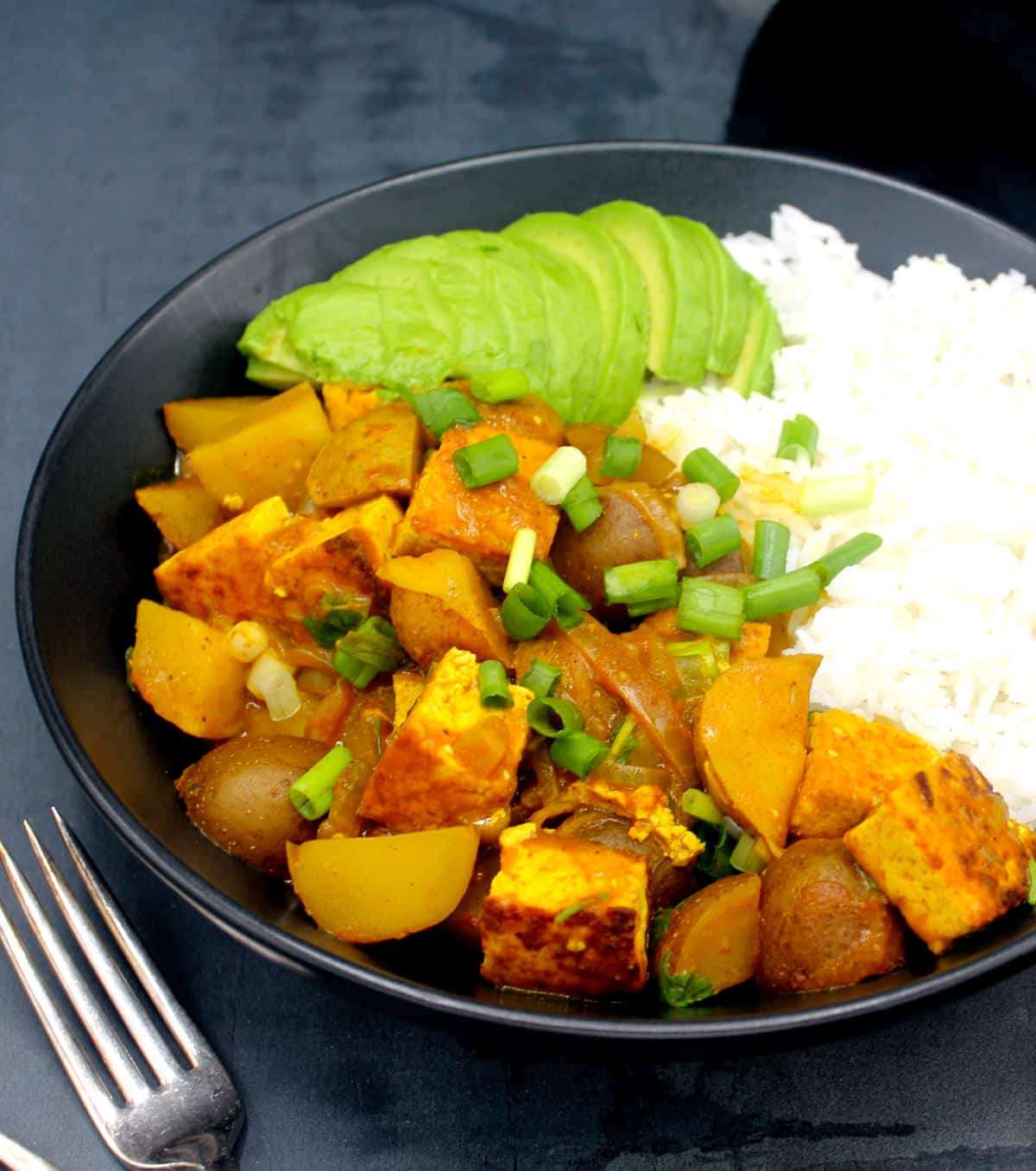 Vegan Jamaican Curry with tofu and potatoes in a black bowl with scallions, avocado and white rice and two forks.