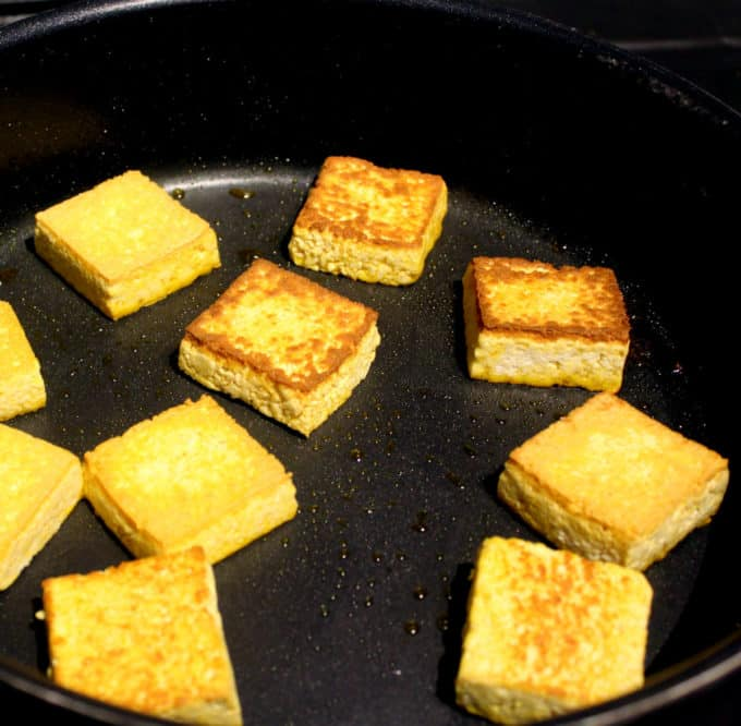 Tofu cubes nicely crusted in a frying pan